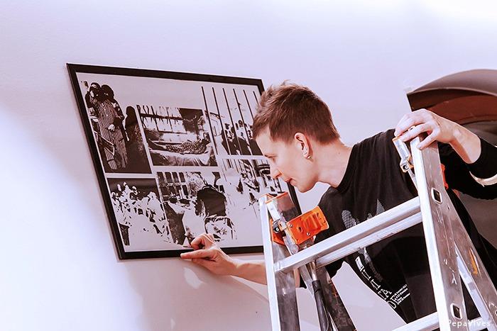 Una persona en lo alto de una escalera colocando un cartel en blanco y negro
